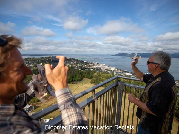 Photo of an adult mail throwing toy airplane off of top of astoria column