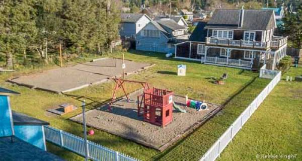 arial view of 1303 yard with playset and house in the background