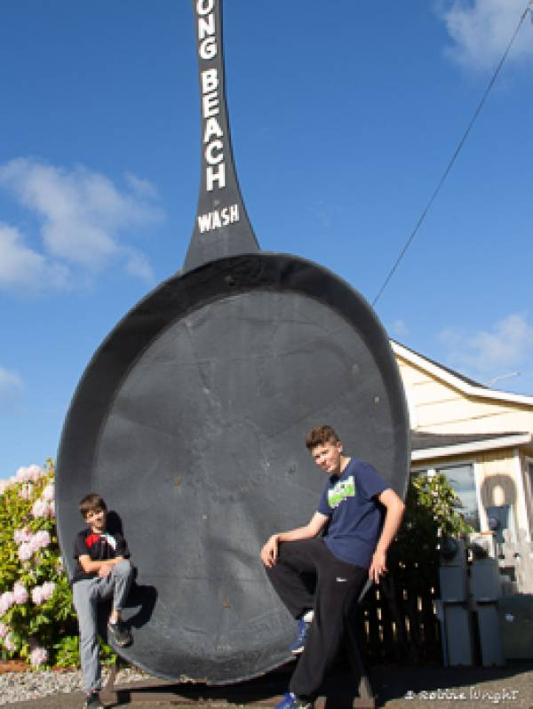 Two kids in front of the Long Beach WA worlds largest Frying Pan