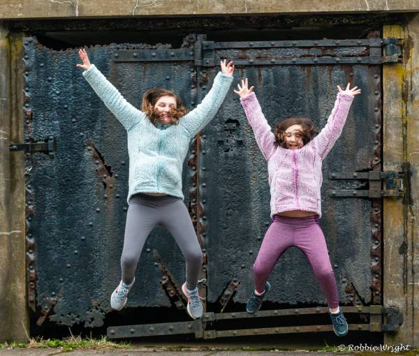 Fort Canby State Parkig two children jumping with joy