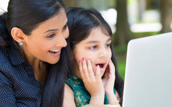 woman and young girl smiling at a computer screen